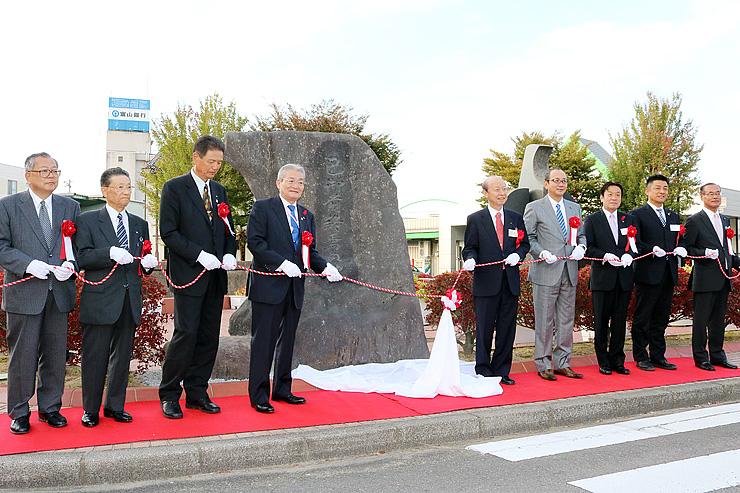 石井知事(左から2人目)らが除幕した巴御前石碑=JR福光駅前