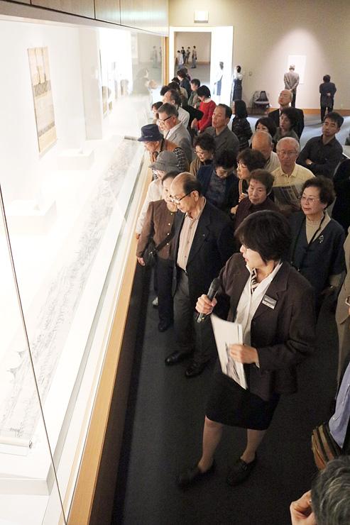 中川課長(手前)の解説を聞きながら、展示替えが迫る「唐土勝景図巻」に見入る来場者たち=県水墨美術館