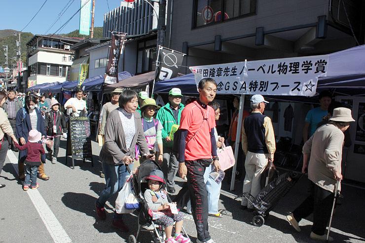 梶田さんのノーベル賞受賞決定に沸く町内を散策する参加者=岐阜県飛騨市神岡町