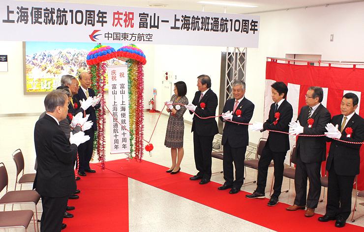 富山-上海便の就航10周年を祝い、式典でくす玉を割る関係者=富山空港
