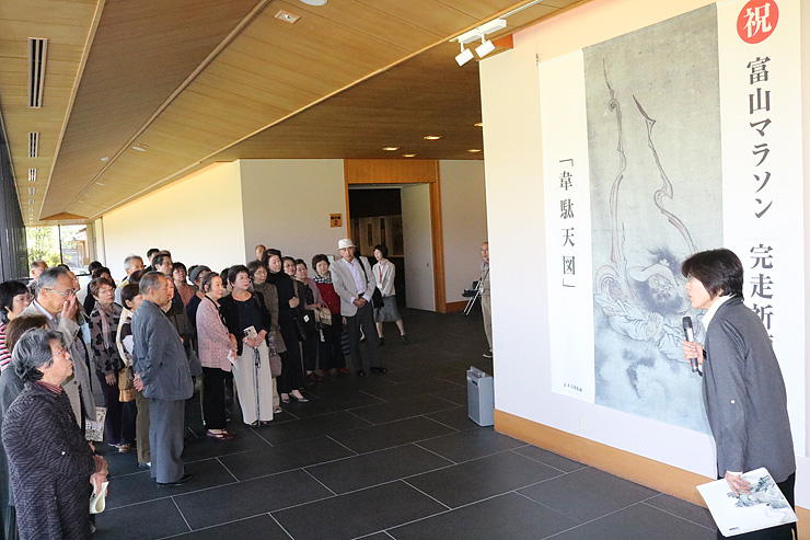 富山マラソンの開催を記念して飾られた韋駄天図のタペストリー。中川学芸課長(右)の解説に大勢が集まり、開催ムードが高まった=県水墨美術館