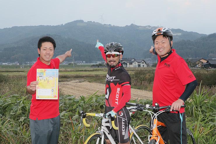 稲葉山(後方)を指さし、自転車レースで多くの人に魅力を発信したいと意気込む飛渡部長(右)ら青年部員=小矢部市内