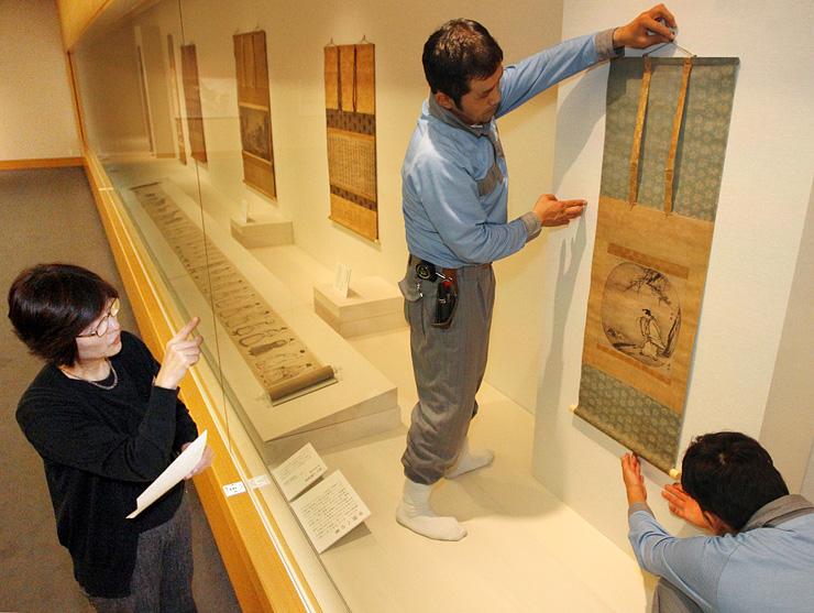 展示替えで雪舟が描いた重要文化財の「倣梁楷黄初平図」を飾り付けるスタッフら=県水墨美術館