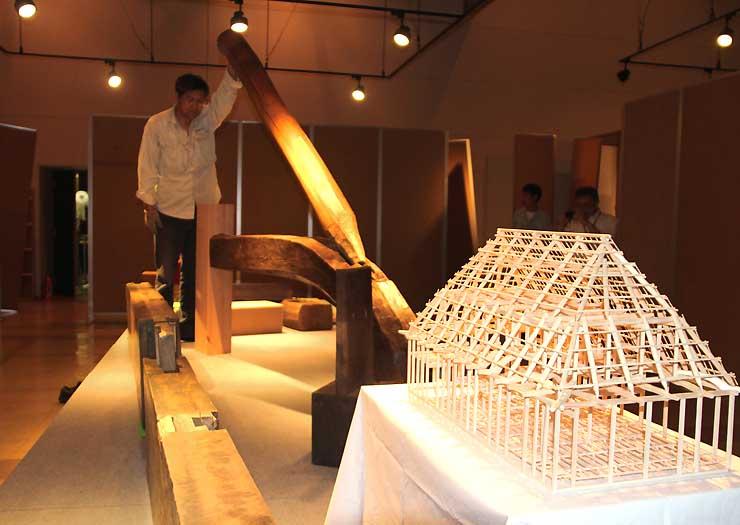 昨年11月の地震で被災した家屋のはり(後方)や住宅の模型が並ぶ企画展会場