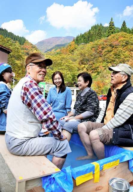 紅葉が進む山々を眺めて足湯を楽しむ行楽客=24日、福井県大野市上打波の鳩ケ湯