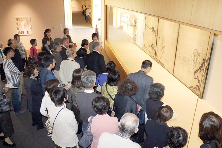ギャラリートークに耳を傾け、等伯の「船子夾山図」に見入る来場者=県水墨美術館