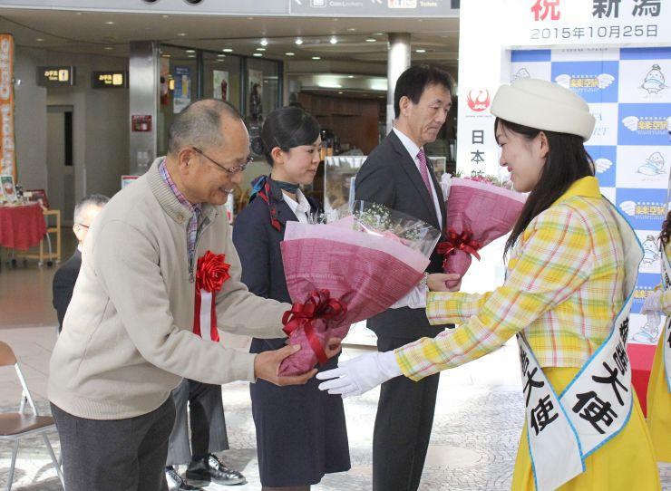 乗客代表らに花束が贈られた新潟-札幌(新千歳)線の増便記念セレモニー=25日、新潟市東区