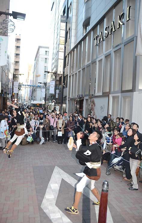 「所望(しょもう)」と呼ばれる祝儀を受けた際に披露する演技で草履を空高く投げる大名行列の役者たち