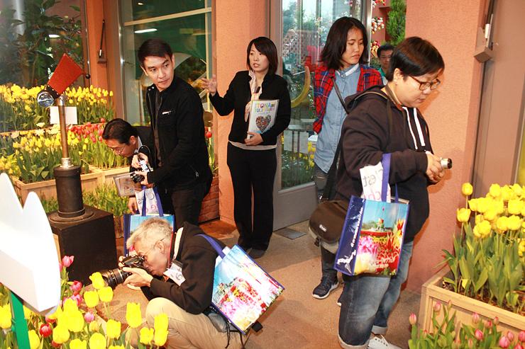 チューリップが咲く館内を取材するタイの記者や編集者ら=チューリップ四季彩館