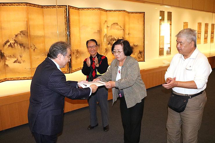 浅地副館長(左)から1万人目の記念品を受け取る横田さん(中央)。奥は、前後に来場した道嶋さん(左から2人目)と上原さん(右)=県水墨美術館