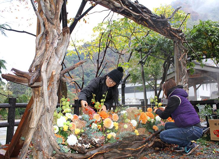 流木や花を使ったアート作品を作る原さん(左)