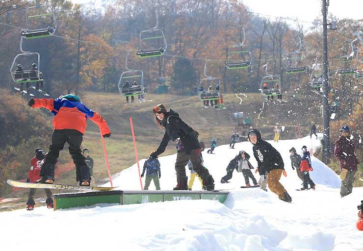 紅葉した木々に囲まれたゲレンデで初滑りを楽しむスノーボーダー=31日午前9時39分、軽井沢町の軽井沢プリンスホテルスキー場