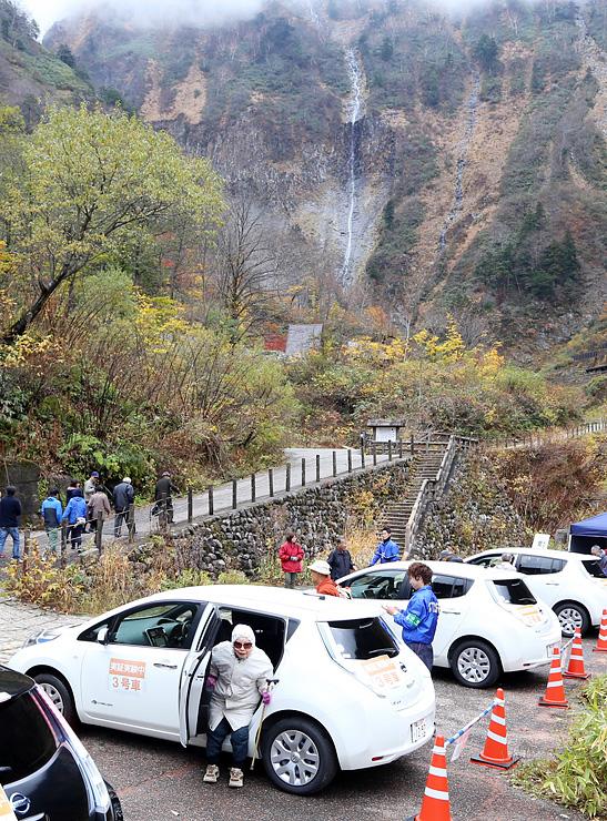 称名滝手前の飛龍橋まで電気自動車で送迎される高齢者ら