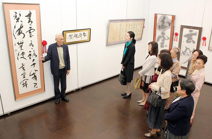 第50回展記念賞に選ばれた森川さん(左)の解説で、院展大賞作を鑑賞する来場者=県民会館美術館