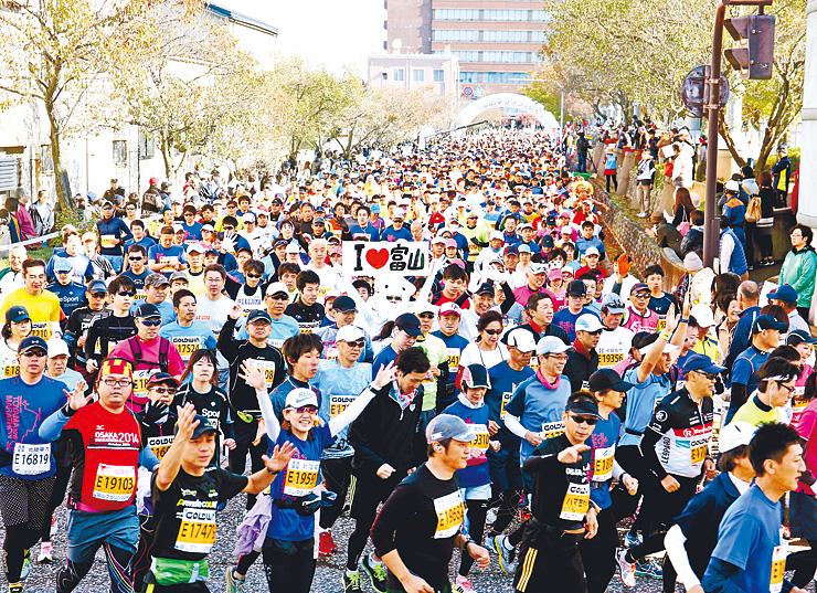号砲とともに一斉にスタートする富山マラソン2015のランナーたち=高岡市役所前