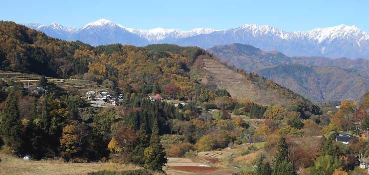 慶師集落(中央左)と鹿島槍ケ岳(右奥)など北アルプスの山々