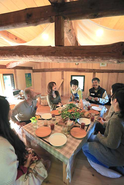 「のらcafe」で遠藤さんが栽培した野菜の料理などを楽しむ人たち。建物の梁(はり)や柱は、明治時代の牛小屋を解体移築したものがそのまま生かされている