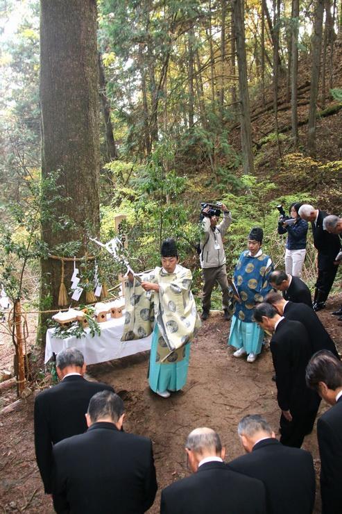 御柱の前で神事をする神主と上片桐地区の役員ら=松川町上片桐
