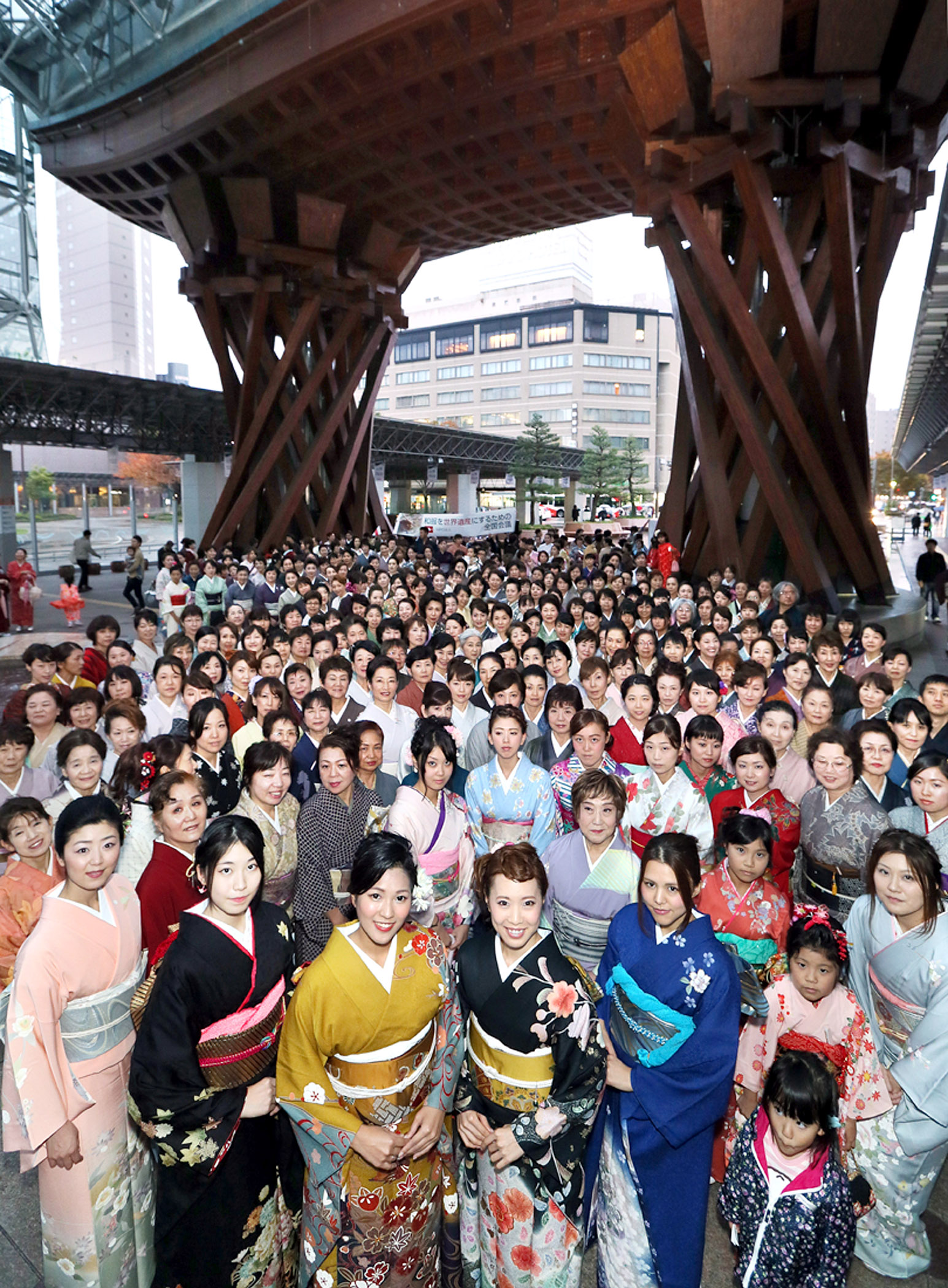 華やかな着物姿で記念撮影する参加者=金沢駅鼓門前
