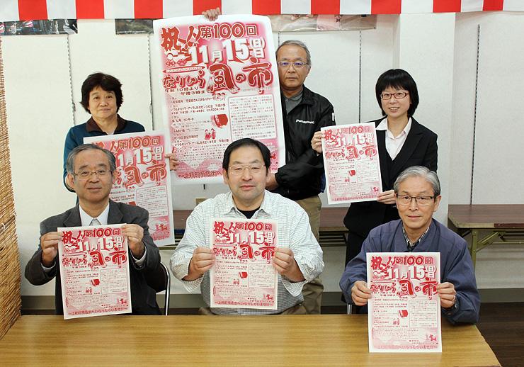 100回目のポスターやチラシを手に笑顔を見せる組合員ら=富山市八尾町上新町