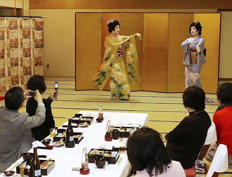 昼食を味わう参加者に舞を披露する芸妓=10日、新潟市中央区