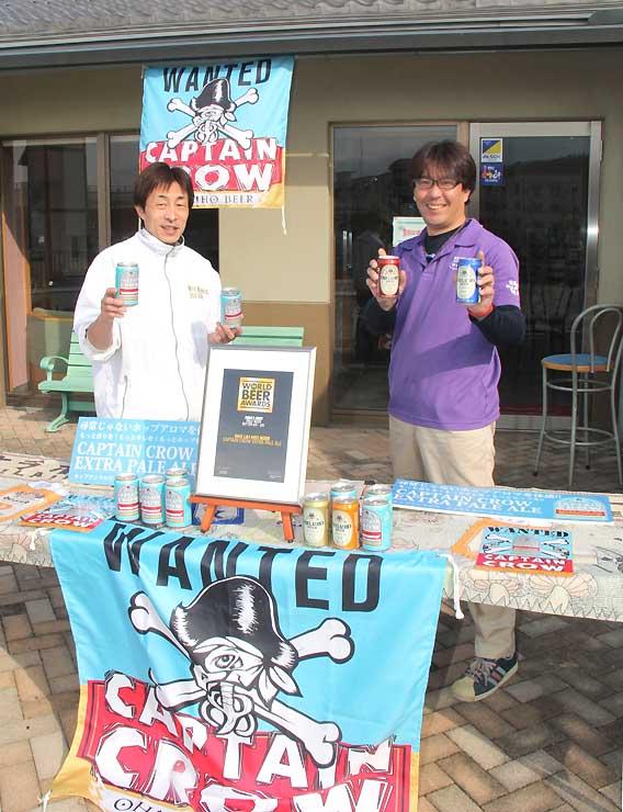 オラホフェスタの会場になるゆうふるtanakaの屋外デッキでオラホビールを持つ久田支配人(右)と山越さん