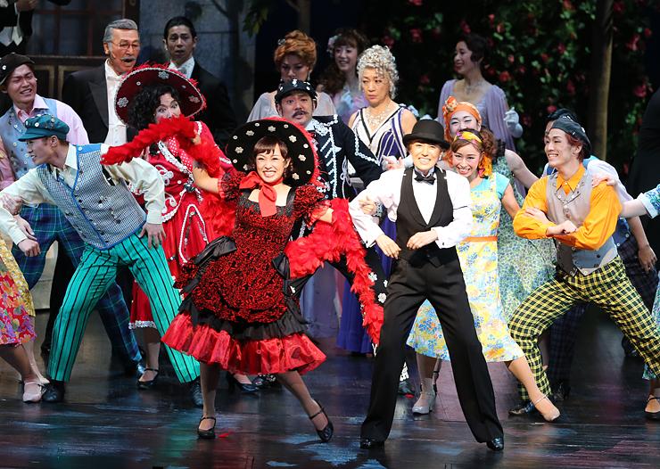 晩さん会の場面で、宝田明さん(後列左から2人目)や中尾ミエさん(同右から2人目)らと一緒にダンスを繰り広げる剣幸さん(前列右)=オーバード・ホール