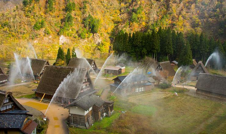 消火訓練で一斉放水のアーチがかかる合掌造り集落=南砺市菅沼