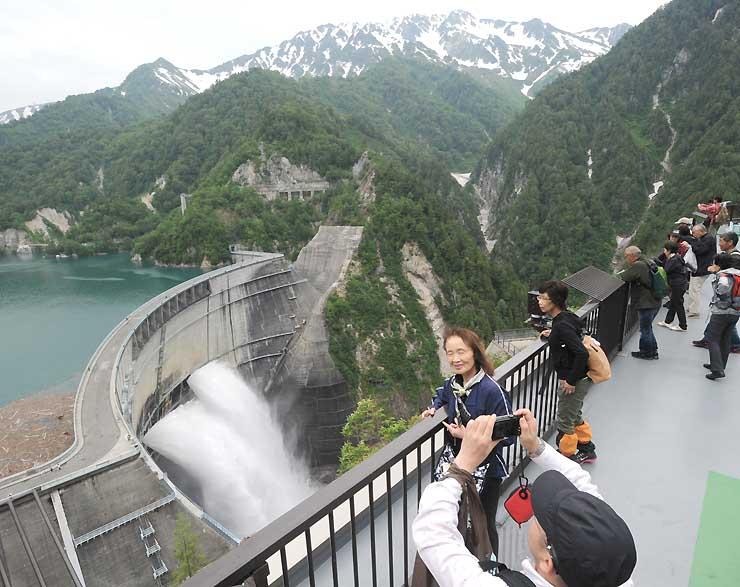 黒部ダムを訪れ、放水を楽しむ観光客たち=6月
