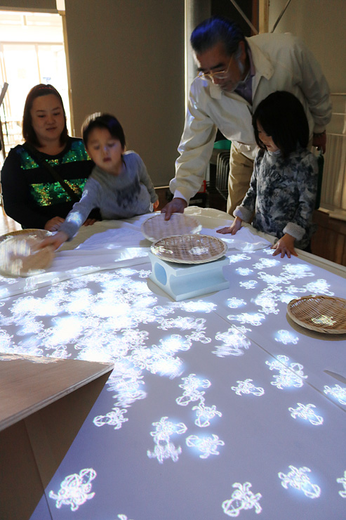 投影されたホタルイカの映像で遊ぶ家族=川の駅新湊