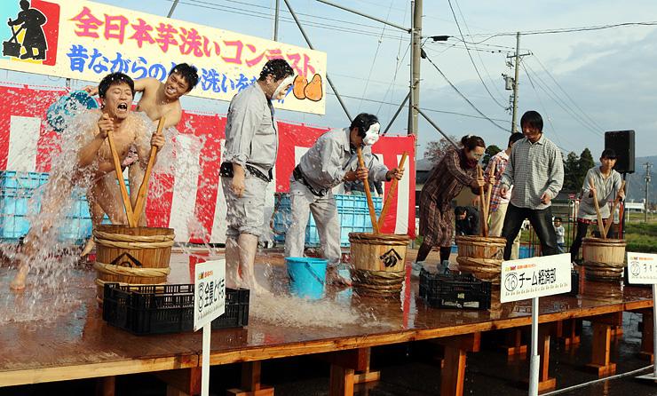 水をかぶるパフォーマンスを交え、芋洗いをする参加者