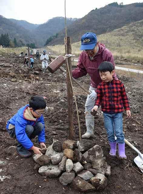 桜の名所を作ろうと苗木を植える参加者=22日、大野市西勝原の旧カドハラスキー場