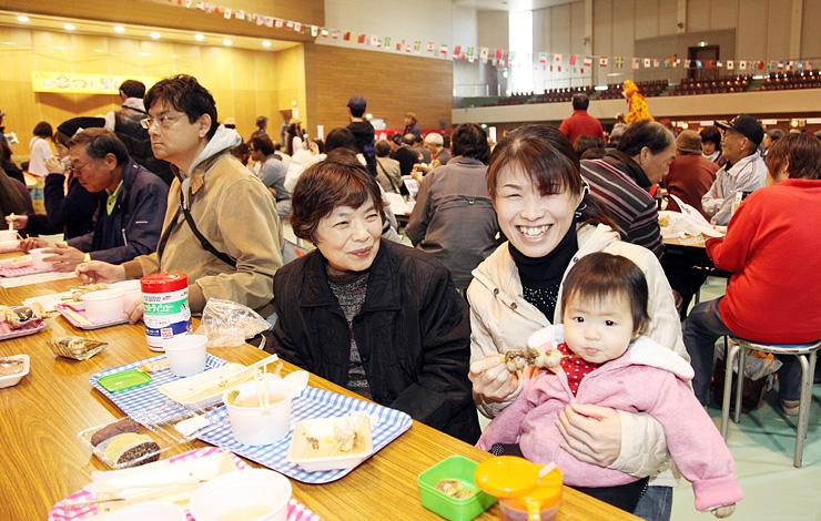 田楽などのサトイモ料理を味わう家族連れ=福野体育館