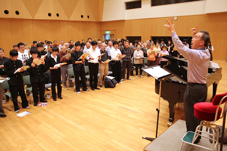 松下理事長(右)の指導で練習に励む団員たち=富山市民芸術創造センター