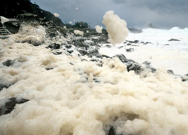 岩場で舞い上がる波の花=27日、福井市鮎川町
