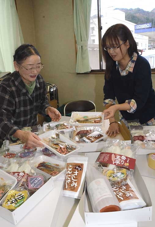 特産品の詰め込み作業をする金子さん(左)ら
