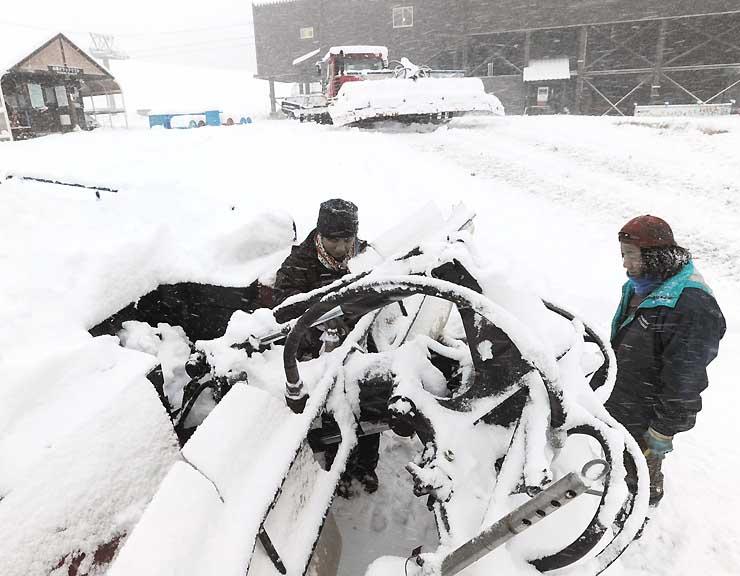 待望の雪が降った栂池高原スキー場で、オープンに向けて圧雪車を調整する従業員=27日、小谷村