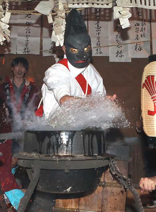 釜の煮え湯を素手ではじく大天狗=2014年12月1日、飯田市南信濃の日月神社