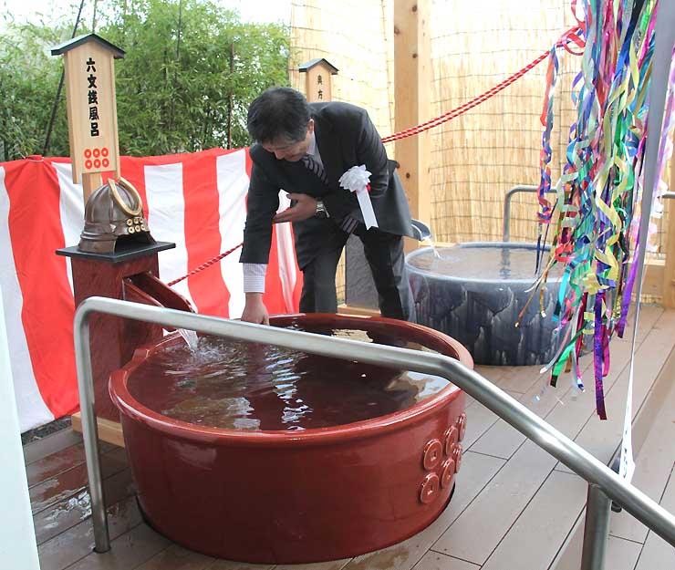 「六文銭風呂」の湯加減を確かめる式典参加者。奥側が「奥方風呂」