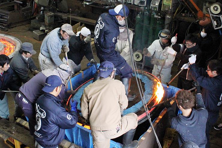 息を合わせて熱した鉄の輪を車輪木地に取り付けるメンバーら=黒田鉄工所