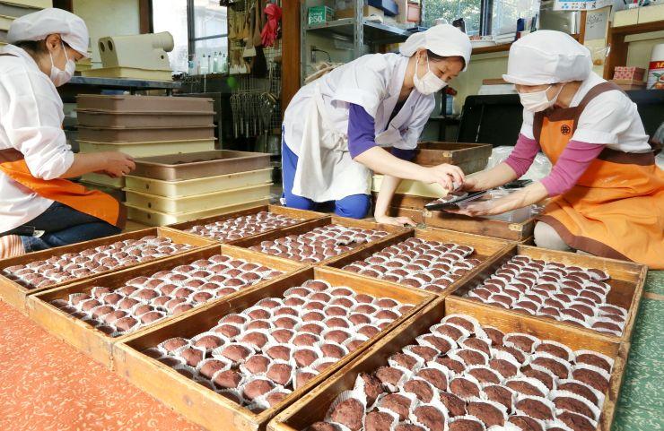 ずらりと並んだ川渡餅。従業員が一つずつパック詰めした=30日、上越市中央1