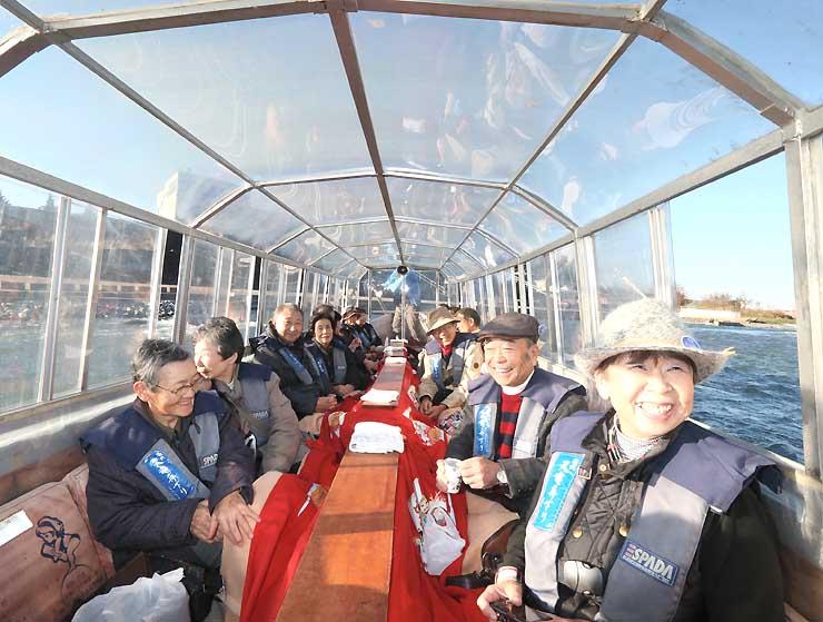 「暖房こたつ舟」に乗って天竜川の景色を楽しむ観光客