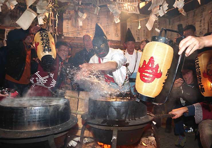 釜の煮え湯を勢いよく素手ではね上げる「大天狗」=1日午後9時56分、飯田市南信濃中立の正一位稲荷神社