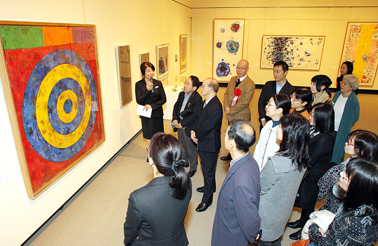 稲塚係長(左)の解説に耳を傾け、現代美術の巨匠の作品に見入る来場者=県立近代美術館
