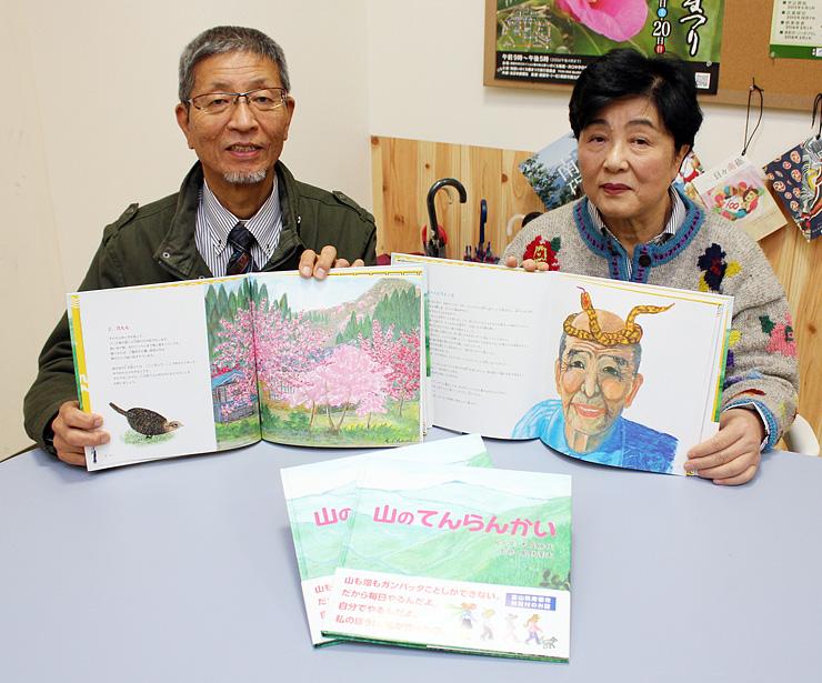 完成した絵本を手にする大成さん(右)と信一さん=南砺市内
