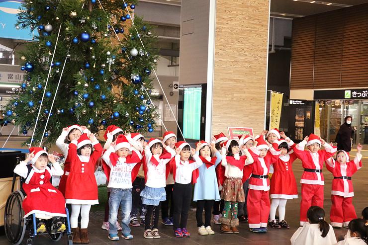 立山杉のクリスマスツリーの前で歌を披露する園児たち=富山駅