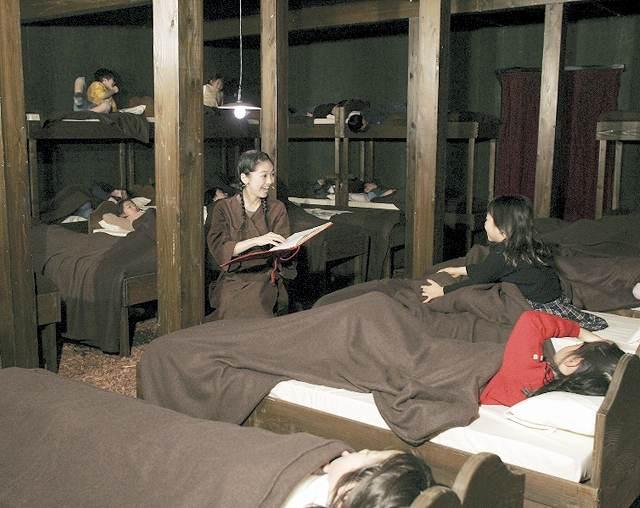 ベッドが並べられた小屋で上演する「親指こぞう」の公演