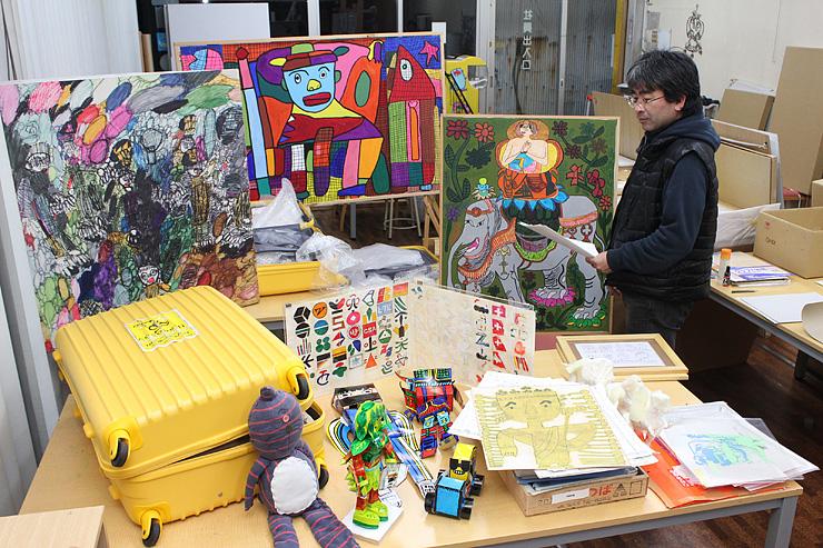 展覧会に向け作品をチェックする米田さん。トランク(左)で届いた県外作家の作品もそろった=高岡市内