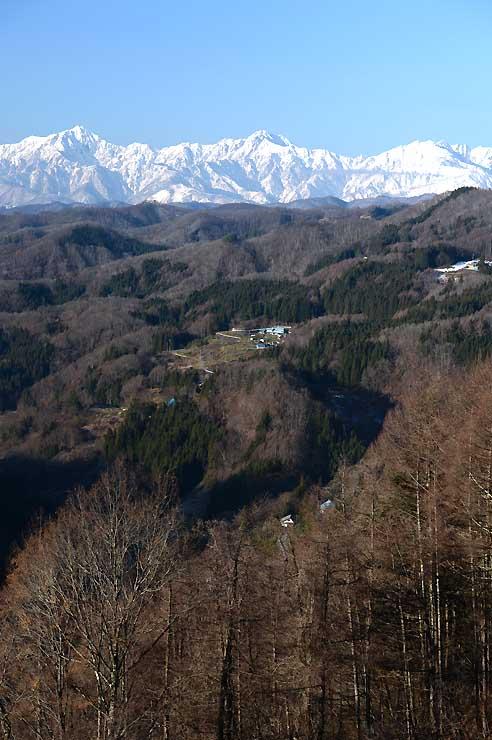 初冬の山里の後方に映える雪化粧した北アルプスの山並み=長野市鬼無里の大望峠
