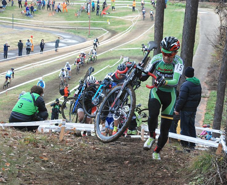 自転車を担いで坂道を駆け上がる選手